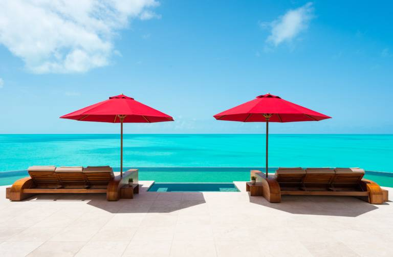 Villa Balinese poolside loungers and umbrellas overlooking Turks and Caicos shore