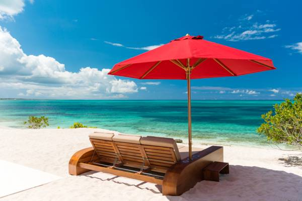 Balinese day beds and large shade umbrellas on beach at Beach Kandi villa