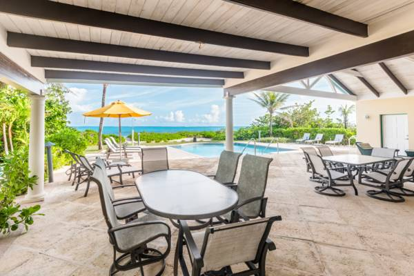 Covered poolside patio facing beach at Serenity House Turks and Caicos